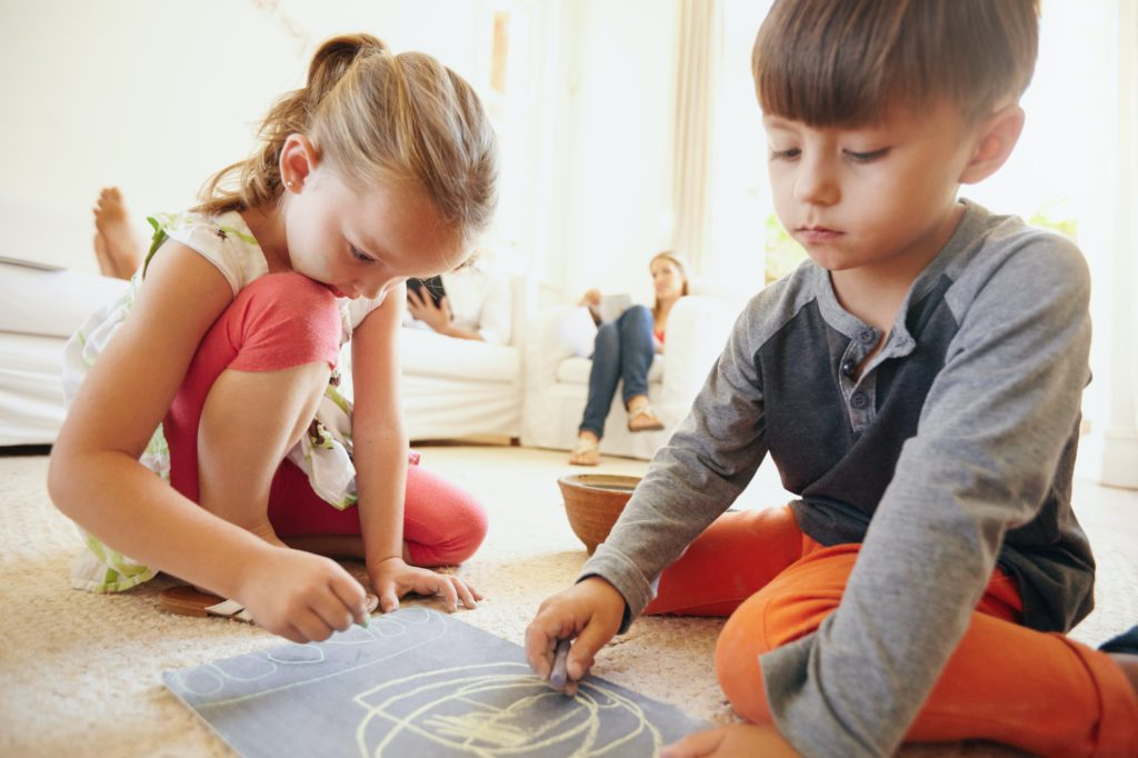 Little children drawing in living room at home